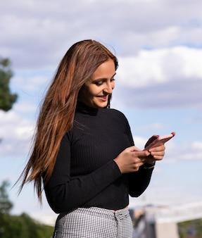 Vrij donkerbruin meisje dat terwijl het babbelen met haar smartphone glimlacht