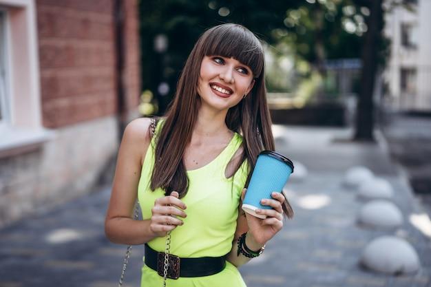 Vrij donkerbruin meisje in groene kleding met kop van koffie lopen openlucht op de straat