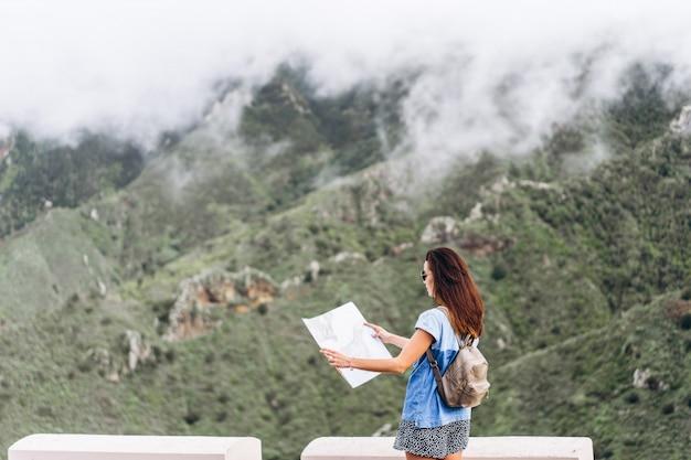 Vrij donkerbruin meisje in zonnebril openlucht in de bergen met kaart.
