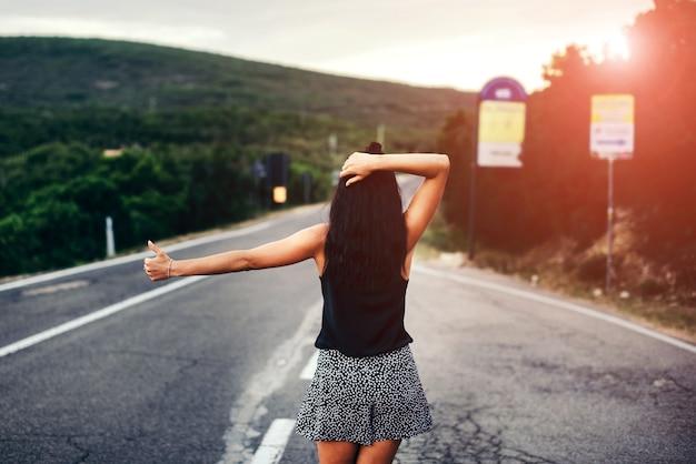 Vrij donkerbruin toeristenmeisje die op de weg lopen donker brunette toeristenmeisje die op de weg lopen