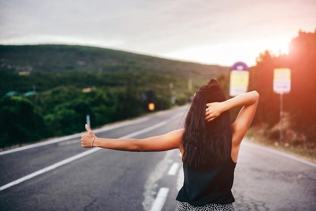Vrij donkerbruin toeristenmeisje die op de weg lopen