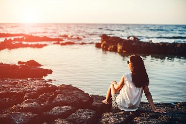 Vrij donkerbruine meisje ontspannen in de stenen