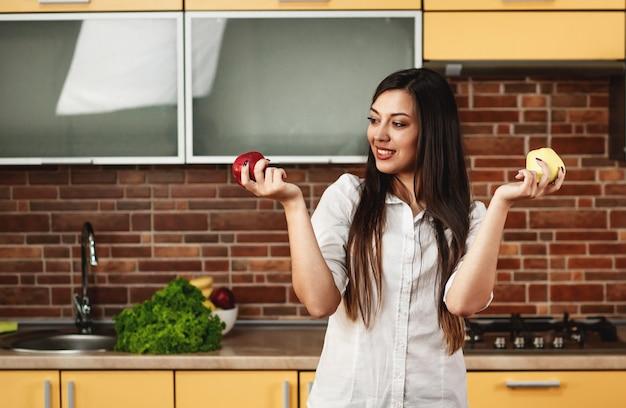 Vrij donkerbruine vrouw bevindt zich in de keuken en houdt twee smakelijke appelen in haar handen. een vrouw kiest welke appel ze wil eten. het concept van voeding en gezond eten, het lichaam reinigen