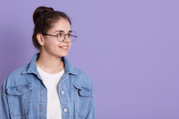 Vrij donkerbruine vrouw die met gelukkige uitdrukking opzij kijkt, die spijkerjasje, wit overhemd en bril draagt, exemplaarruimte voor reclame of promotietekst.