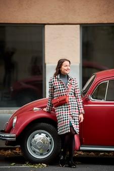 Vrij donkerbruine vrouw die op rode retro auto leunt en de afstand met zoete glimlach bekijkt