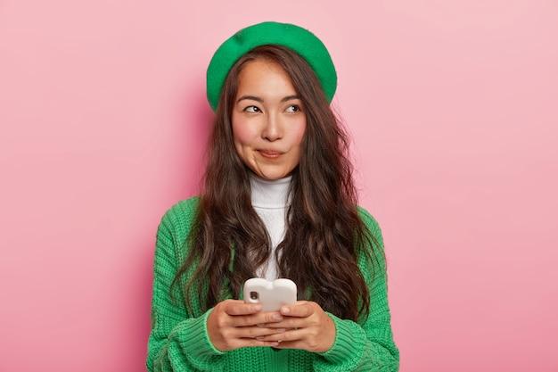 Vrij donkerharige japanse vrouw gebruikt moderne mobiele telefoon voor het verzenden van tekstberichten, surft op internet, heeft een doordachte uitdrukking