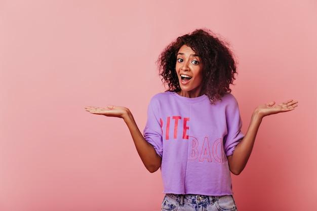 Vrij donkerogig zwart meisje dat zich op roze bevindt. vrolijke kortharige vrouw in paars shirt met verbazing.
