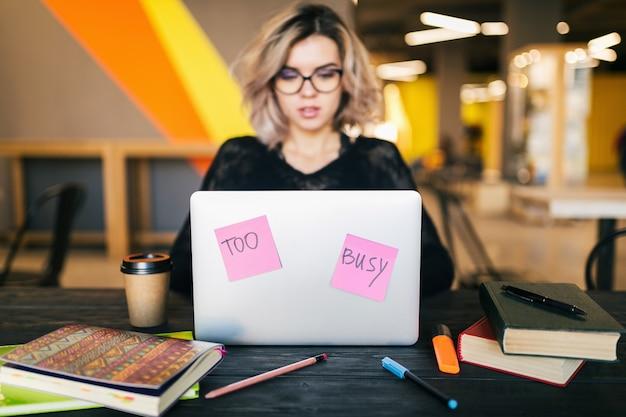 Vrij drukke jongedame zittend aan tafel bezig met laptop in co-working office, papieren stickers, dragen van een bril, overleg, student in de klas