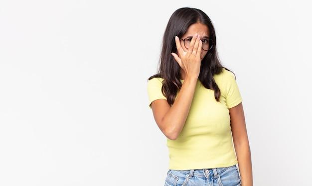 Vrij dunne spaanse vrouw die zich verveeld, gefrustreerd en slaperig voelt na een vermoeiende