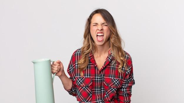 Vrij dunne vrouw die agressief schreeuwt, erg boos kijkt en een koffiethermoskan vasthoudt