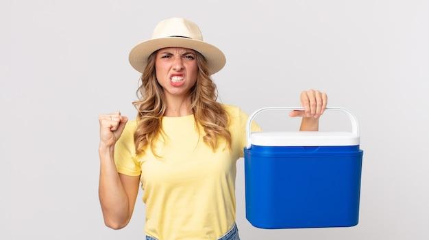Vrij dunne vrouw die agressief schreeuwt met een boze uitdrukking en een zomerpicknickkoelkast vasthoudt