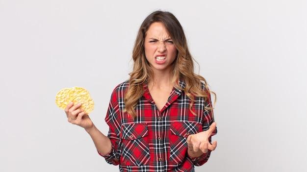 Vrij dunne vrouw die boos, geïrriteerd en gefrustreerd kijkt en een dieetrijstwafels vasthoudt