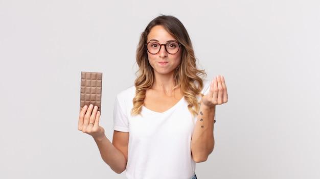 Vrij dunne vrouw die capice of geldgebaar maakt, zegt dat je moet betalen en een chocoladereep vasthoudt