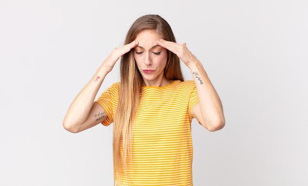 Vrij dunne vrouw die er gestrest en gefrustreerd uitziet, onder druk werkt met hoofdpijn en last heeft van problemen