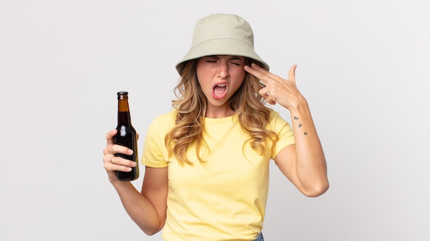 Vrij dunne vrouw die er ongelukkig en gestrest uitziet, zelfmoordgebaar maakt een pistoolteken en houdt een biertje vast. zomer concept