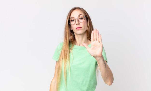 Vrij dunne vrouw die er serieus, streng, ontevreden en boos uitziet en een open hand laat zien die een stopgebaar maakt