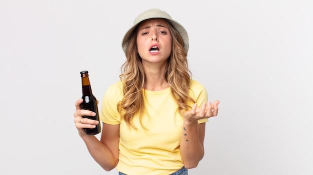 Vrij dunne vrouw die er wanhopig, gefrustreerd en gestrest uitziet en een biertje vasthoudt. zomer concept