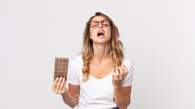 Vrij dunne vrouw die er wanhopig, gefrustreerd en gestrest uitziet en een chocoladereep vasthoudt
