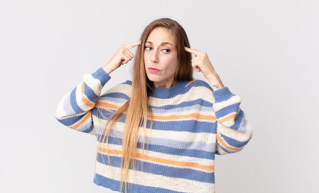 Vrij dunne vrouw die geconcentreerd kijkt en hard nadenkt over een idee, zich een oplossing voor een uitdaging of probleem voorstellend