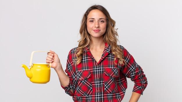 Vrij dunne vrouw die gelukkig glimlacht met een hand op de heup en zelfverzekerd en een theepot vasthoudt