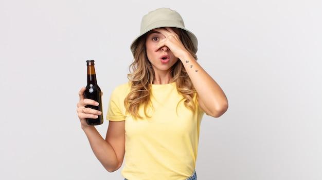 Vrij dunne vrouw die geschokt, bang of doodsbang kijkt, haar gezicht bedekt met de hand en een biertje vasthoudt. zomer concept