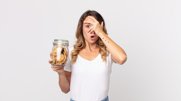 Vrij dunne vrouw die geschokt, bang of doodsbang kijkt, haar gezicht bedekt met de hand en een glazen fles met koekjes vasthoudt