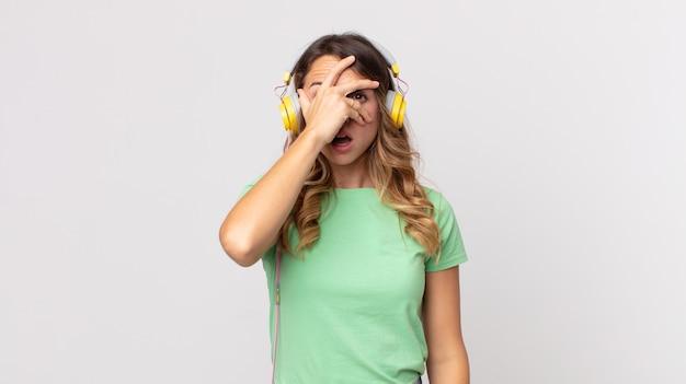 Vrij dunne vrouw die geschokt, bang of doodsbang kijkt, haar gezicht bedekt met hand die muziek luistert met een koptelefoon