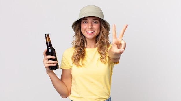 Vrij dunne vrouw die lacht en er gelukkig uitziet, gebaart naar overwinning of vrede en een biertje vasthoudt. zomer concept