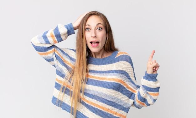 Vrij dunne vrouw die lacht, er blij, positief en verrast uitziet en een geweldig idee realiseert dat naar de laterale kopieerruimte wijst