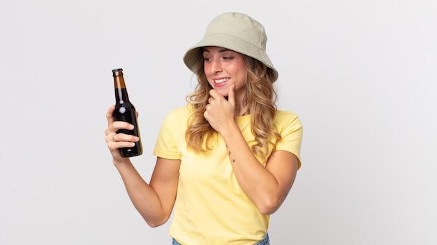 Vrij dunne vrouw die lacht met een gelukkige, zelfverzekerde uitdrukking met de hand op de kin en een biertje vasthoudt. zomer concept