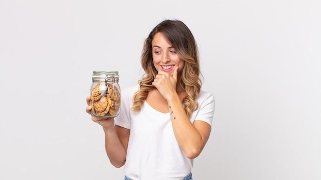 Vrij dunne vrouw die lacht met een gelukkige, zelfverzekerde uitdrukking met de hand op de kin en een glazen fles met koekjes vasthoudt