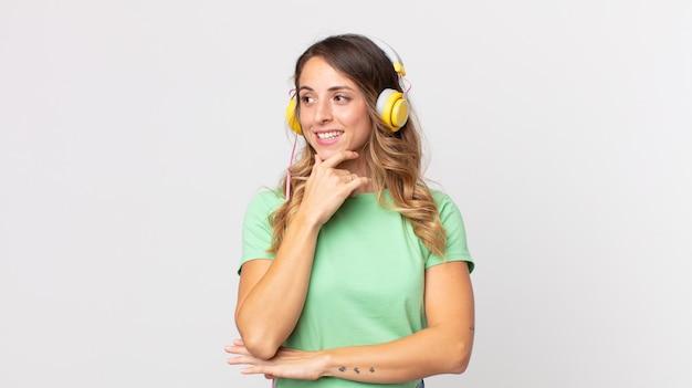 Vrij dunne vrouw die lacht met een gelukkige, zelfverzekerde uitdrukking met de hand op de kin en luistert naar muziek met een koptelefoon