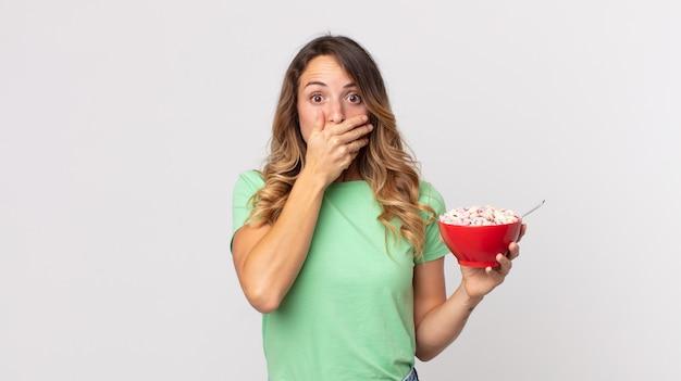 Vrij dunne vrouw die mond bedekt met handen met een geschokte en een ontbijtkom vasthoudt