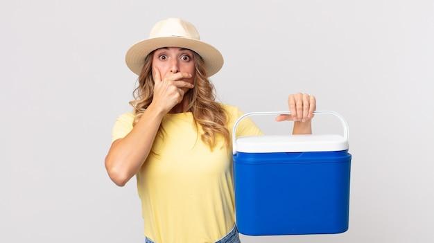 Vrij dunne vrouw die mond bedekt met handen met een geschokte en een zomerpicknickkoelkast vasthoudt