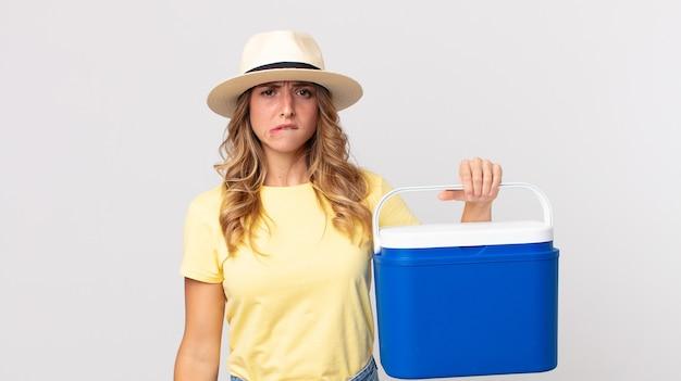 Vrij dunne vrouw die verbaasd en verward kijkt en een zomerpicknickkoelkast vasthoudt