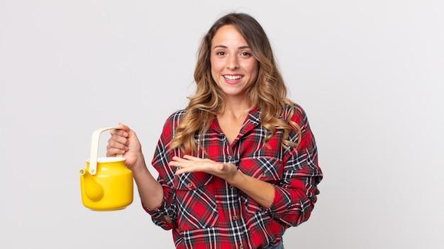 Vrij dunne vrouw die vrolijk lacht, zich gelukkig voelt en een concept toont en een theepot vasthoudt