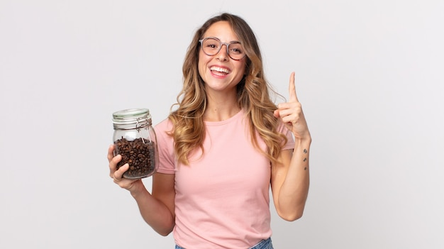 Vrij dunne vrouw die zich een gelukkig en opgewonden genie voelt nadat ze een idee heeft gerealiseerd en een fles koffiebonen vasthoudt