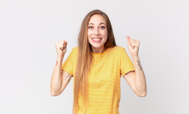 Vrij dunne vrouw die zich gelukkig, verrast en trots voelt, schreeuwt en succes viert met een grote glimlach