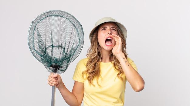 Vrij dunne vrouw die zich gelukkig voelt, een grote schreeuw geeft met de handen naast de mond die een hoed draagt en een visnet vasthoudt