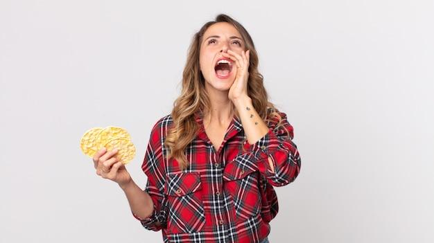 Vrij dunne vrouw die zich gelukkig voelt, een grote schreeuw geeft met de handen naast de mond en een dieetrijstwafels vasthoudt