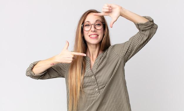 Vrij dunne vrouw die zich gelukkig, vriendelijk en positief voelt, lacht en een portret of fotolijst maakt met handen