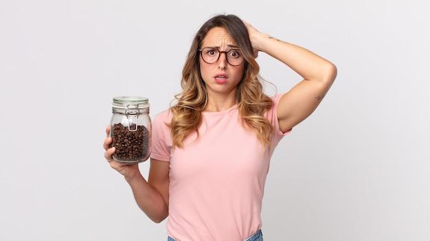 Vrij dunne vrouw die zich gestrest, angstig of bang voelt, met de handen op het hoofd en een fles koffiebonen vasthoudt