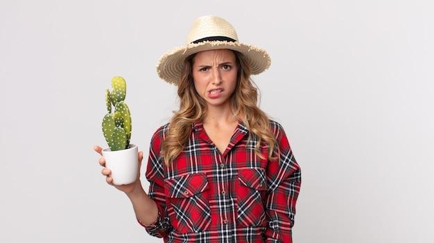 Vrij dunne vrouw die zich verbaasd en verward voelt terwijl ze een cactus vasthoudt. boer concept