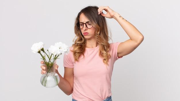 Vrij dunne vrouw die zich verward en verward voelt, haar hoofd krabt en decoratieve bloemen vasthoudt
