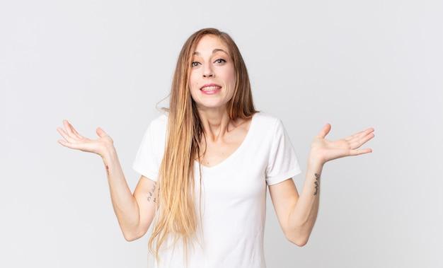 Vrij dunne vrouw die zich verward en verward voelt, twijfelt, weegt of verschillende opties kiest met grappige uitdrukking