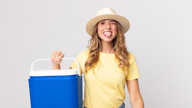 Vrij dunne vrouw met vrolijke en rebelse houding, grappen makend en tong uitsteken en een zomerpicknickkoelkast vasthouden