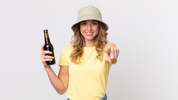 Vrij dunne vrouw wijzend op de camera die jou kiest en een biertje vasthoudt. zomer concept