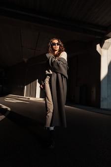 Vrij elegant jong vrouwenmodel met krullend haar en zonnebril in een lange modieuze jas loopt op straat