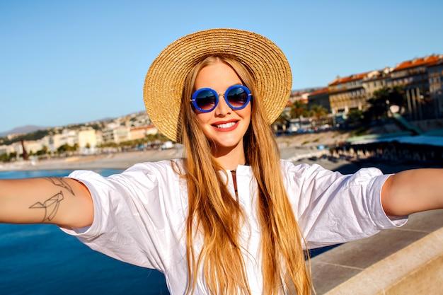 Vrij elegante blonde mooie vrouw selfie vooraan maken op mooi strand