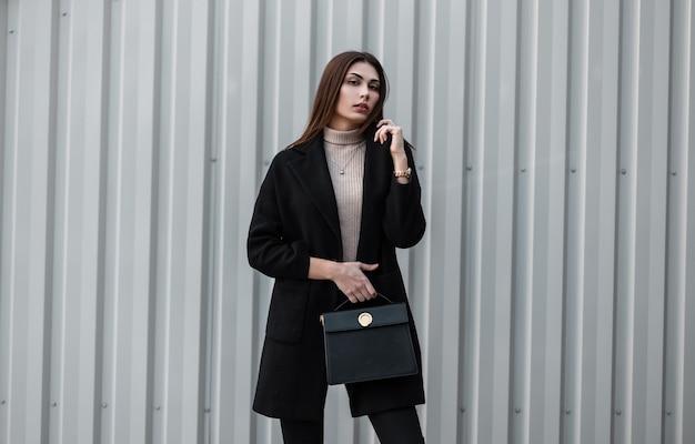 Vrij elegante jonge vrouw mannequin met lang haar in zwarte lente trendy jas met modieuze lederen zwarte handtas staat in de buurt van een vintage metalen muur in de stad. leuk luxe meisje. stedelijke dame